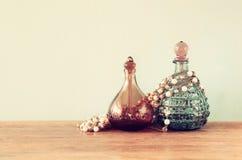 葡萄酒antigue香水瓶,在木桌上 减速火箭的被过滤的图象 图库摄影