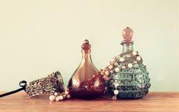 葡萄酒antigue香水瓶,在木桌上 减速火箭的被过滤的图象 免版税库存图片
