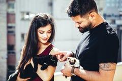 葡萄酒tonned拿着他们的猫的愉快的夫妇的图象 库存照片