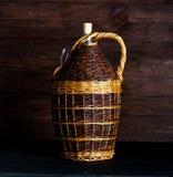 葡萄酒Wickered藤瓶 柳条包裹了在木桌上的玻璃瓶 图库摄影