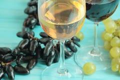 葡萄,一杯在一蓝色木backgrounnut的酒秋天农业葡萄酒土气饮料 图库摄影