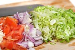 董事会干酪剪切把蔬菜切成小方块 免版税库存照片