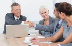 董事在证券交易经纪人行情室会议的握手 免版税库存图片