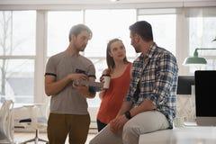 董事谈论在数字式片剂,当食用咖啡时 免版税库存照片