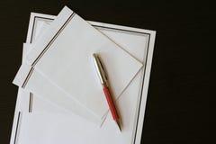 葬礼在黑桌上的通知(卡片)和信封 免版税库存图片