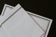 葬礼在黑桌上的通知(卡片)和信封 库存照片