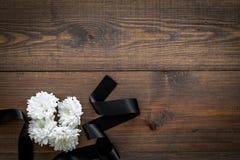 葬礼标志 在黑丝带附近的白花在文本的黑暗的木背景顶视图空间 库存图片