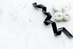 葬礼标志 在黑丝带附近的白花在白色石头背景顶视图拷贝空间 免版税图库摄影