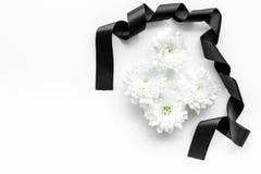 葬礼标志 在黑丝带附近的白花在白色背景顶视图拷贝空间 免版税库存照片