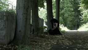 葬礼礼服的遭受的哀悼的妇女在她的在她死的心爱的感觉遗憾和哀痛坟墓的膝盖  股票录像