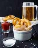 洋葱圈,番茄酱,海盐,啤酒 免版税库存照片
