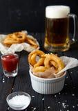 洋葱圈,番茄酱,海盐,啤酒 库存图片