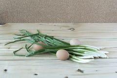 葱用木表面上的鸡蛋 免版税库存图片