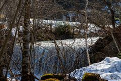 蒂罗尔州基希贝格,提洛尔/奥地利- 2019年3月24日:小河和低瀑布射击通过树和灌木在 免版税图库摄影