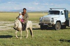 蒙古人在马背上乘坐与孩子, Harhorin,蒙古 免版税图库摄影