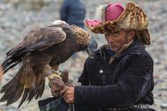 蒙古哈萨克人老鹰猎人传统衣物,拿着在他的胳膊的一只鹫在沙漠山 免版税图库摄影