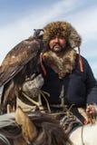 蒙古哈萨克人老鹰猎人传统衣物,拿着在他的胳膊的一只鹫在瓦剌沙漠山  免版税库存照片