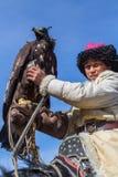 蒙古哈萨克人老鹰猎人传统衣物,拿着在他的胳膊的一只鹫在瓦剌沙漠山  库存照片