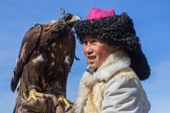 蒙古哈萨克人老鹰猎人传统衣物,拿着在他的胳膊的一只鹫 免版税库存照片