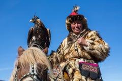 蒙古哈萨克人老鹰猎人传统衣物,拿着在他的胳膊的一只鹫 库存图片