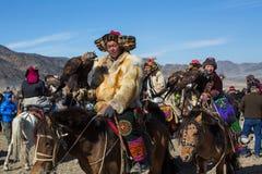 蒙古哈萨克人老鹰猎人传统衣物,拿着在他的胳膊的一只鹫 库存照片