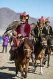 蒙古哈萨克人老鹰猎人传统衣物,拿着在他的胳膊的一只鹫 免版税库存图片