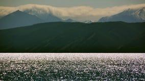 蒙古在湖Hovsgol闪闪发光银色天际岸,萨彦岭的晚上第一雪在夏天 库存图片