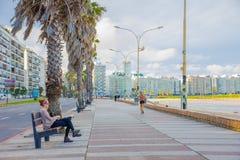 蒙得维的亚,乌拉圭- 2016年5月04日:享受在委员会海岸的人们下午与城市作为背景 免版税图库摄影