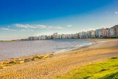 蒙得维的亚,乌拉圭- 2016年5月04日:在海滩的好的日落与作为背景的一些大厦 免版税库存图片