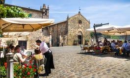 蒙特里久尼,意大利, 2015年5月30日-侍者在旅游餐馆的服务食物在有圣玛丽亚的Assunta大广场 免版税库存照片