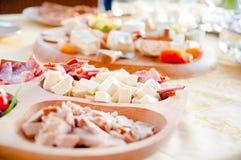 蒜味咸腊肠、乳酪和熏火腿开胃菜在晚上吃午餐 库存图片