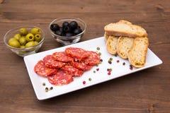 蒜味咸腊肠和橄榄开胃小菜在木头 免版税库存图片