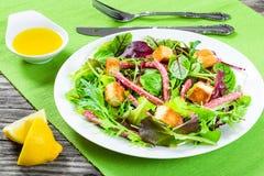 蒜味咸腊肠和混杂的莴苣叶子-婴孩菠菜,芝麻菜,在一个白色盘的唐莴苣在老木桌上, t可口新鲜的沙拉  免版税库存图片
