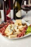 蒜味咸腊肠用不同的肉类和乳酪产品的承办酒席盛肉盘和在桌上的不同的酒-开胃菜 免版税库存图片