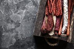 蒜味咸腊肠用在一个老盘子的香料 在深灰背景 图库摄影