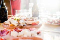 蒜味咸腊肠,酒,乳酪,熏火腿开胃菜用caprese沙拉 免版税库存图片