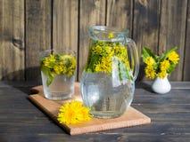 蒲公英与新鲜的黄色开花的煎药茶在茶杯里面,在木桌上 免版税库存照片