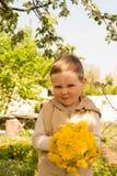 蒲公英花束对于儿童` s手 拿着蒲公英的手在草甸开花花束 选择聚焦 库存图片