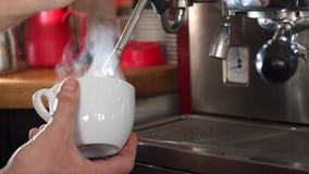 蒸加奶咖啡杯子的一男性barista的特写镜头在咖啡馆 : 股票视频