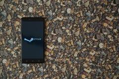 蒸在智能手机的商标在小石头背景  免版税库存照片