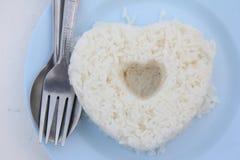 蒸在蓝色盘的米与心脏形状 免版税库存图片