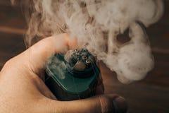 蒸气云彩从RDA的vaping的在人手、电子现代的vape或ecig设备上 库存图片