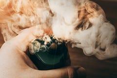 蒸气云彩从RDA的vaping的在人手、电子现代的vape或ecig设备上 免版税图库摄影