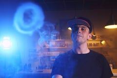 蒸气云彩的Vaping人在vape酒吧的 库存图片