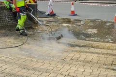 蒸汽喷嘴在sidwalk的洗涤擦净剂 免版税库存图片