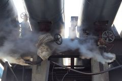蒸汽漏出在热管道的 蒸外出从有阀门的生锈的管 免版税图库摄影