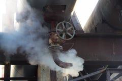 蒸汽漏出在热管道的 蒸外出从有阀门的生锈的管 库存照片
