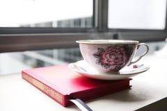 蒸汽的茶杯,被安置在书顶部 免版税库存照片