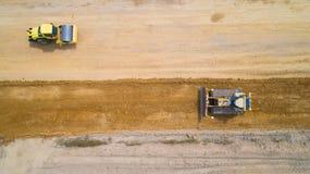 蒸汽路辗和一台推土机的空中照片在建造场所 库存图片