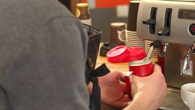 蒸热的热奶咖啡的Barista牛奶在机器在咖啡馆 股票录像